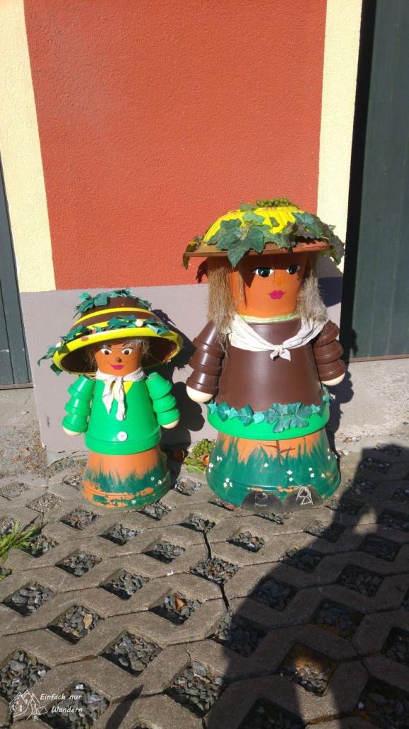Zwei Blumentopffiguren am Wegesrand sind schön bemalt und als Mutter und Kind verziert.