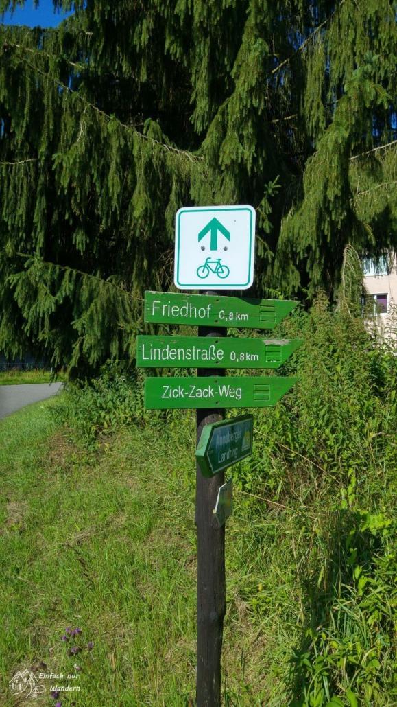 """Ein Wegweiser zeigt verschiedene Möglichkeiten an, auch den """"Zick-Zack-Weg""""."""