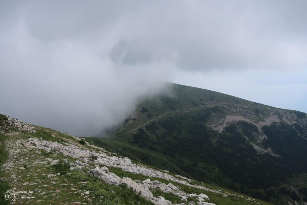 Einige Wolken drücken am Bergkamm von der anderen Seite hoch.
