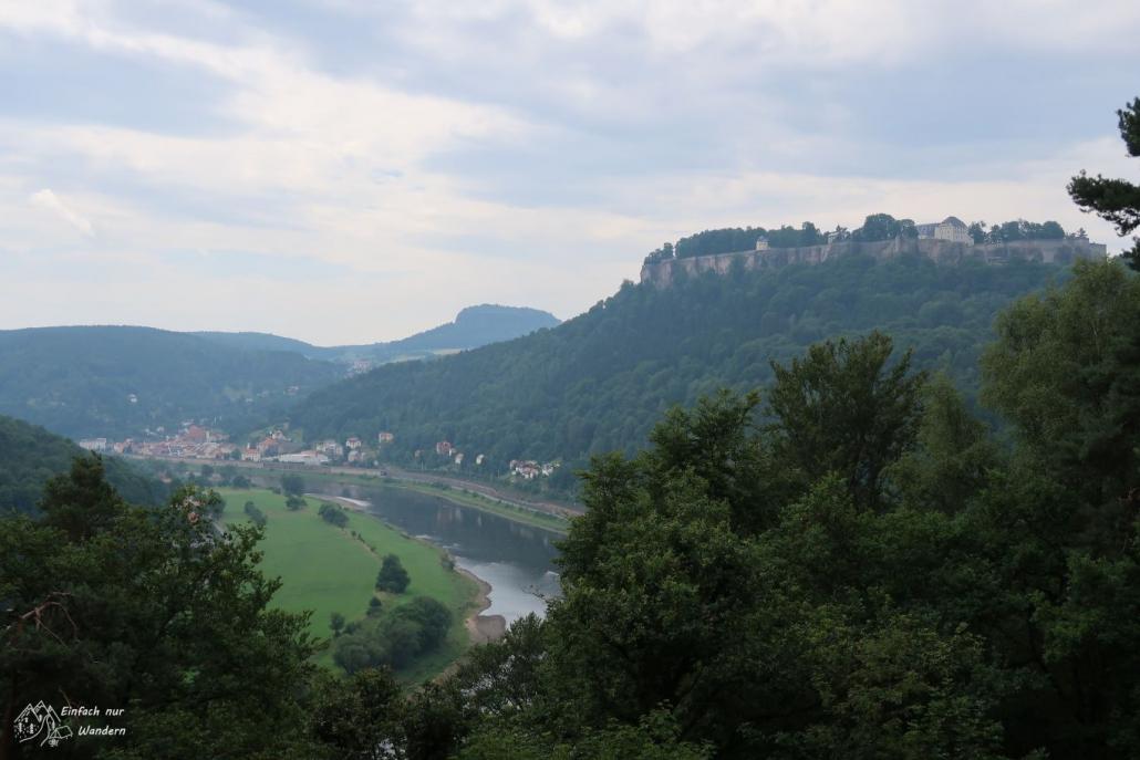 Die durch den Maler Johann-Alexander Thiele gemalte Aussicht. Über Bäume hinweg sieht man die Festung Königstein über der Elbe thronen.