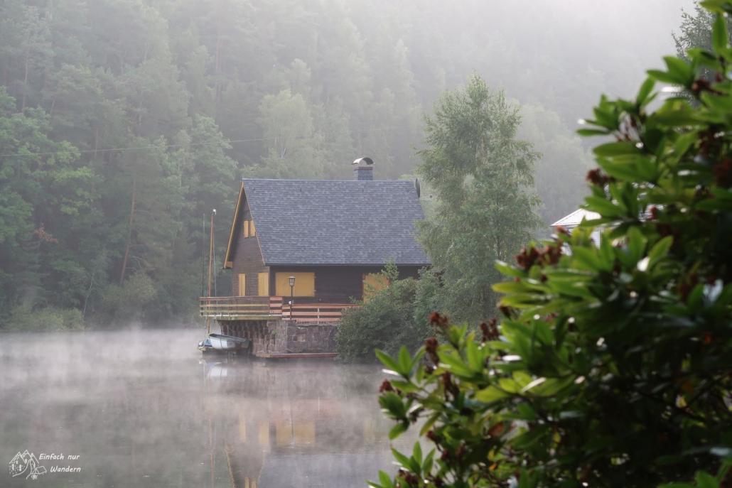 Mystische Stimmung am Morgen mit Nebel zeigt ein Haus direkt am Ufer.