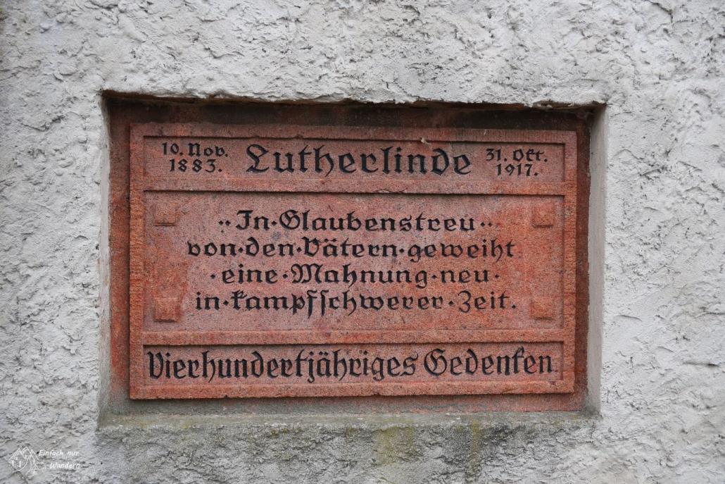 Eine Gedenktafel einer Lutherlinde ist an eine Kirchenmauer angebracht zum vierhundertjährigen Gedenken.