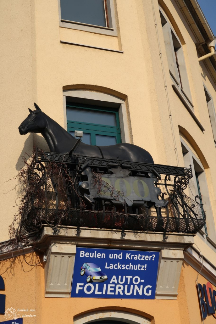 Auf einem Balkon eines Hauses steht eine schwarze Pferdeskulptur, was lustig aussieht.