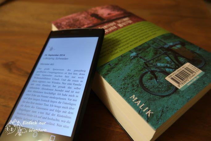 Die Rückseite des Buches Wandern, Radeln, Paddeln und ein Smartphone liegen nebeneinander.