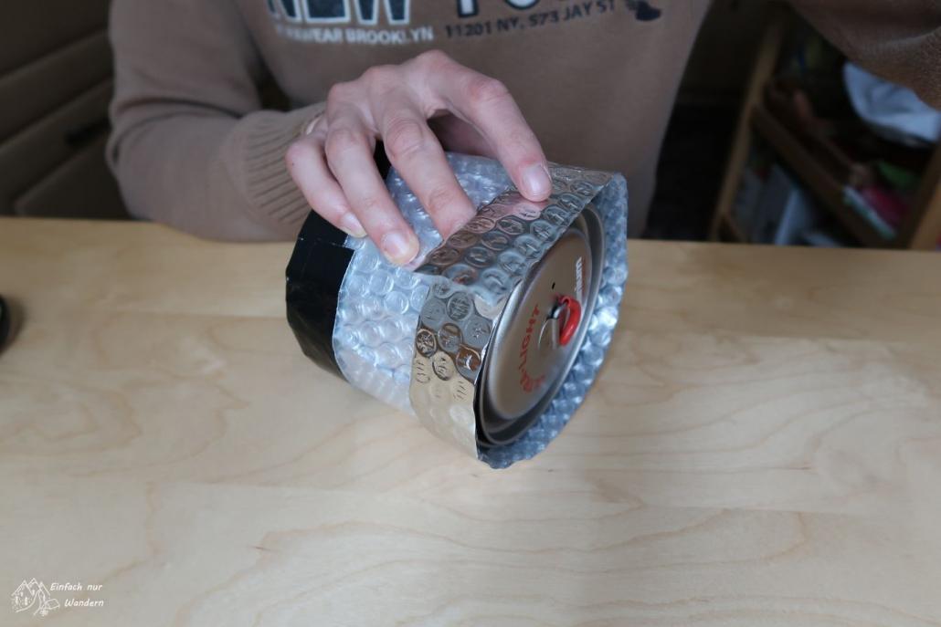 Unser Topf steckt nun im halbfertigen Pot Cozy. EIn schmaler Streifen wird um alles gelegt, um erneut den Aussendurchmesser zu ermitteln.