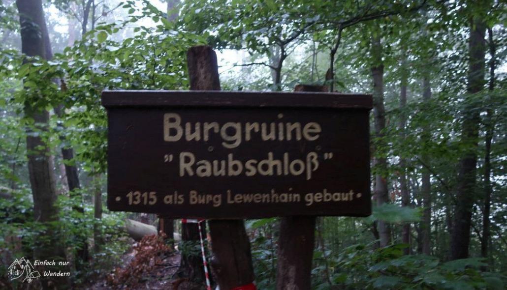 Auf einem Schild steht: Burgruine Raubschloss.